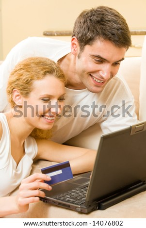 Young happy couple paying by credit card in internet shop