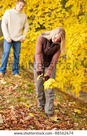 Young happy couple picking leaves in autumn park playful