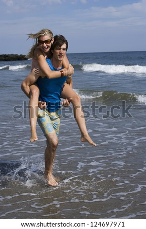 Young happy couple piggybacking on seashore