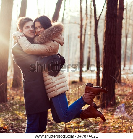 Young happy couple posing in sunny winter forest  - stock photo