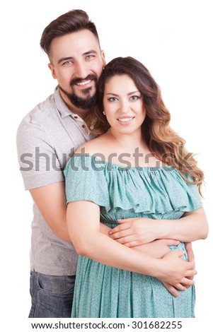 Young happy couple pregnant woman smiling over white background. Studio shooting. Isolated. Happy familly
