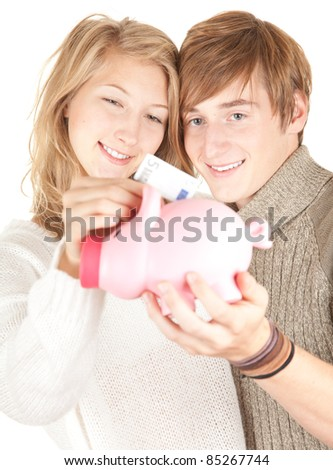 young happy couple putting five euro in piggy bank - stock photo