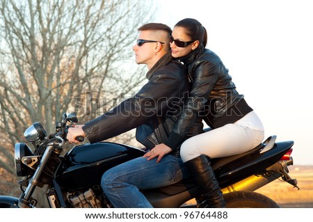 Young happy couple ready to go on a ride with motorcycle on beautiful autumn day. - stock photo
