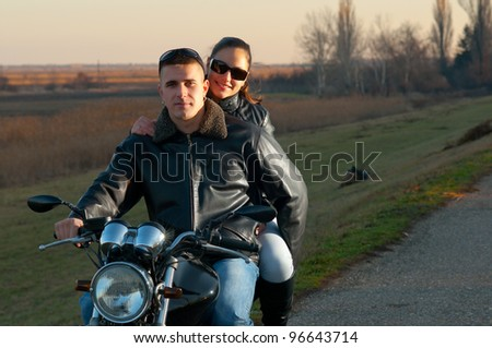 Young happy couple riding a motorcycle at sunset on beautiful autumn day. - stock photo