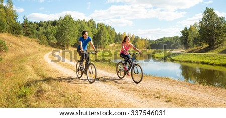 Young Happy Couple Riding Bicycles by the River. Healthy Lifestyle Concept.  - stock photo