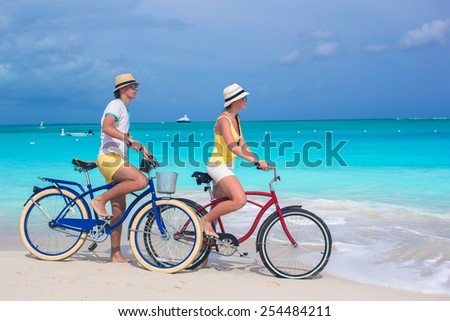 Young happy couple riding bikes on white tropical beach - stock photo