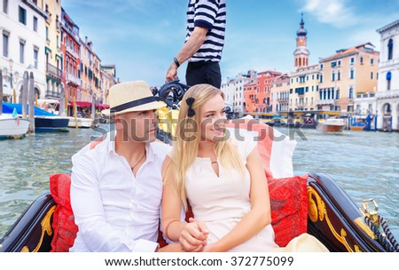 Young happy couple riding on a gondola on Grand Canal in Venice, spending honeymoon in Italy, Europe - stock photo