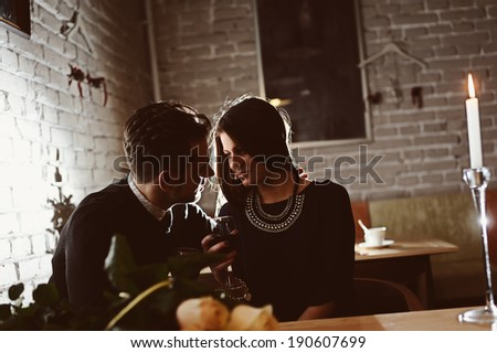 Young happy couple romantic date drink glass of red wine at restaurant - stock photo