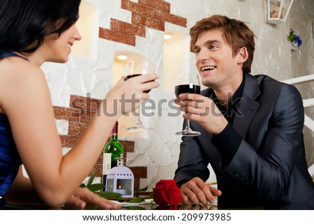 Young happy couple romantic date drink glass of red wine at restaurant, celebrating valentine day - stock photo