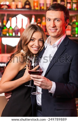 Young happy couple romantic date. man and woman holding wine and standing in restaurant - stock photo