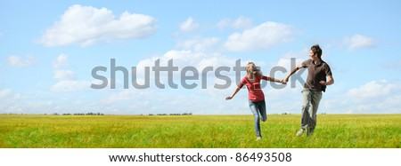 Young happy couple running on a green meadow with blue cloudy sky on the background - stock photo