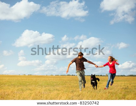 Young happy couple running on a meadow with a dog - stock photo
