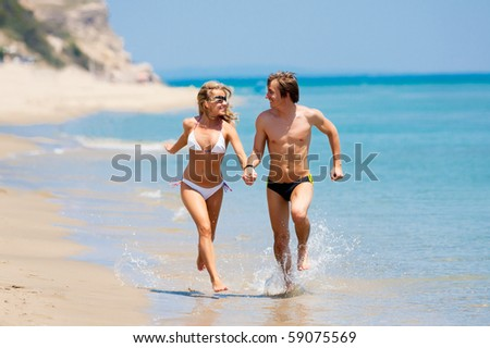 Young happy couple running on the beach - stock photo