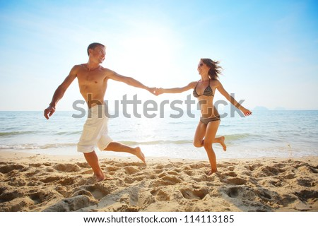 Young happy couple running together among a beach at sunny day - stock photo