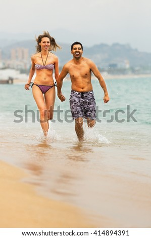 Young happy couple runs at the beach near the sea
