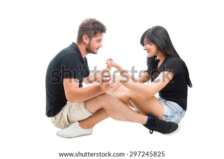 Young happy couple sitting and facing each other while holding hands as lovers on a date - stock photo