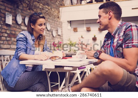 Young happy couple sitting at cafe - stock photo