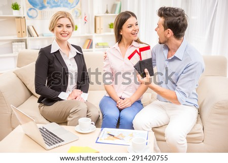 Young happy couple sitting at tourist agency and holding tickets. - stock photo
