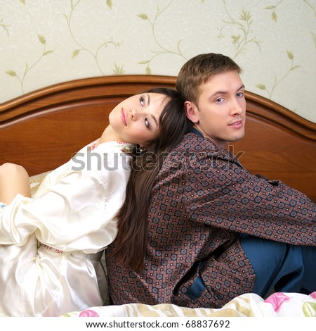 Young happy couple sitting back to back on the bed - stock photo