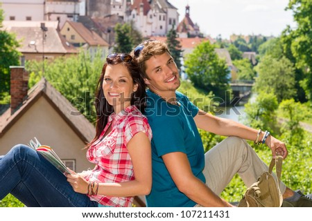 Young happy couple sitting city view smiling travel vacation - stock photo