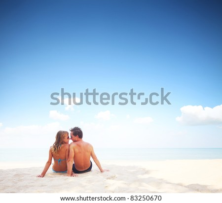 Young happy couple sitting on a sand by sea and enjoying each other - stock photo
