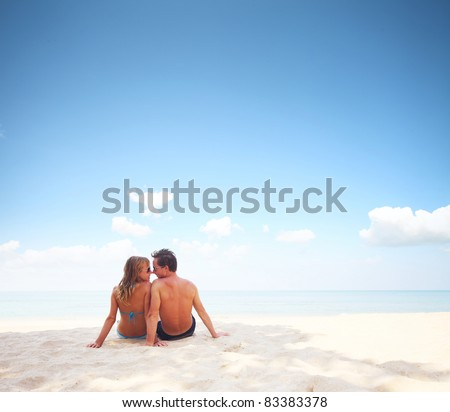 Young happy couple sitting on a sand by sea and enjoying each other