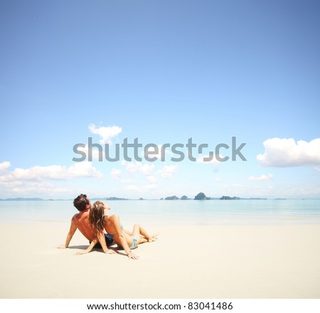 Young happy couple sitting on a sand by sea and looking to a sky