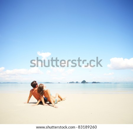 Young happy couple sitting on a sand by sea and looking to a sky - stock photo