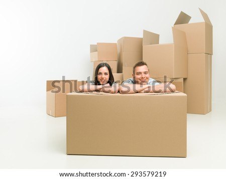 young happy couple sitting on floor in new apartment with moving boxes in background - stock photo