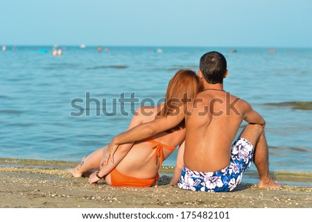 Young happy couple sitting on sandy beach and embracing