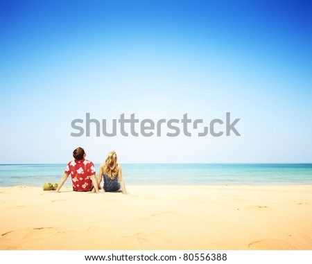 Young happy couple sitting on yellow sand by blue sea and looking to a clear sky - stock photo