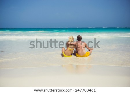 Young happy couple sitting together on a sand by sea and looking to a horizon - stock photo