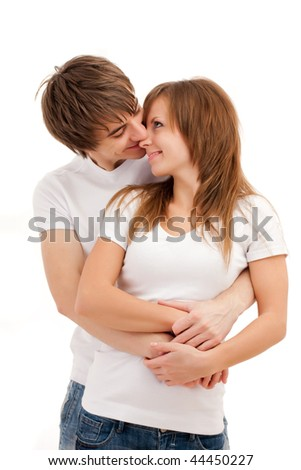Young happy couple smiling and cuddling. Casual wear. Isolated over white - stock photo