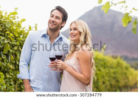 Young happy couple smiling and looking in the distance in the grape fields
