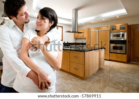 Young happy couple smiling at kitchen of new house - stock photo
