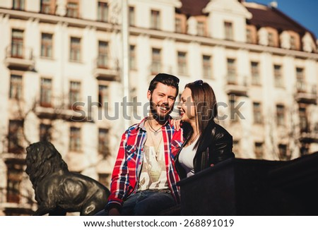 young happy couple smiling while sitting on the background of the city - stock photo