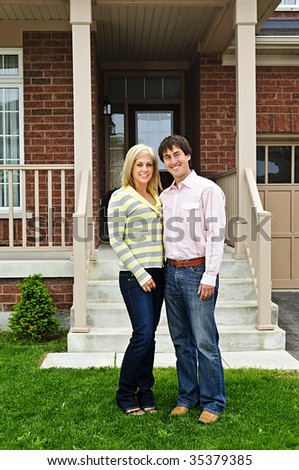 Young happy couple standing in front of house - stock photo