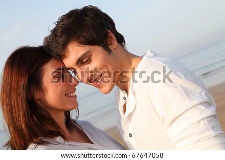 Young happy couple standing on a beach