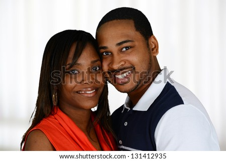 Young happy couple standing together inside their home - stock photo