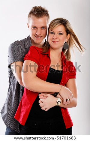 Young happy couple stands on white background - stock photo