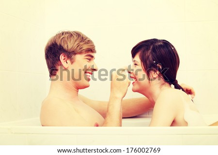 Young happy couple taking bath together.  - stock photo