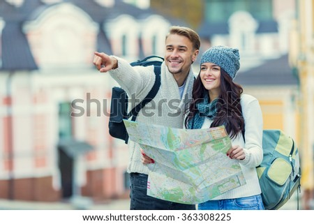 Young happy couple traveling with maps in hand in the city - stock photo
