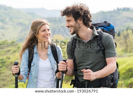 Young Happy Couple Trekking In Countryside - stock photo