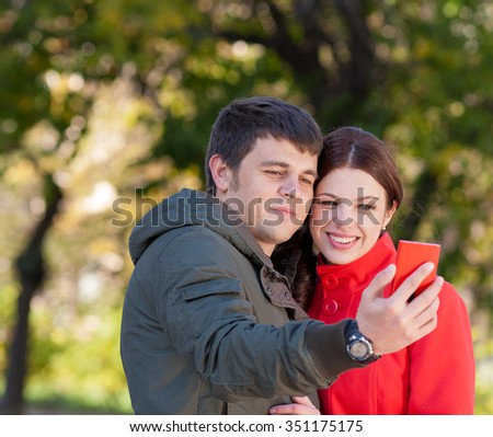 Young happy couple using mobile phone in park - stock photo