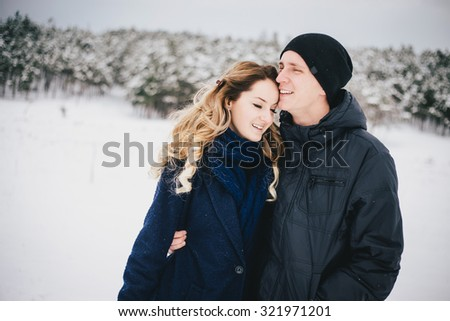 Young happy couple walking in a winter countryside