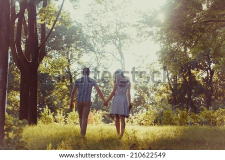 Young happy couple walking in the park, back view, unfocused - stock photo
