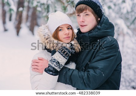 young happy couple walking in winter snowy forest, wearing warm knitted gloves with christmas ornament