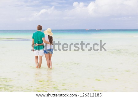 Young happy couple walking on beach holding around each other. - stock photo