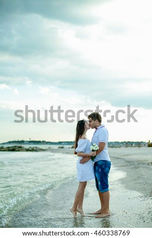 Young happy couple walking on beach smiling holding around each other. Love story