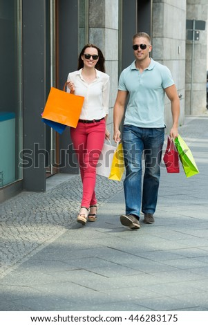 Young Happy Couple Walking On Footpath Holding Multi-colored Shopping Bags - stock photo